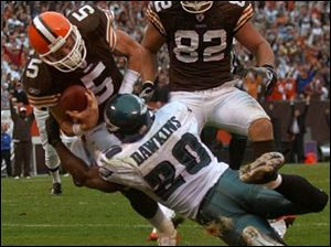 Cleveland quarterback Jeff Garcia bowls over Philadelphia's Brian Dawkins to score a touchdown from four yards out in the fourth quarter, helping the Browns tie the Eagles 31-31 before losing in overtime.