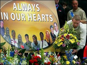 An employee places flowers at a memorial site at the Hendrick Motorsports headquarters in Concord, N.C.