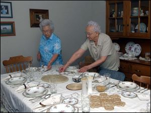 Marge, left, and Alta Grieser set the table in their duplex for an auctioned dinner.
