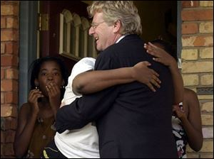 A surprised Winthrop Street resident gives Jerry Springer a big hug when the celebrity shows up unannounced at her door.