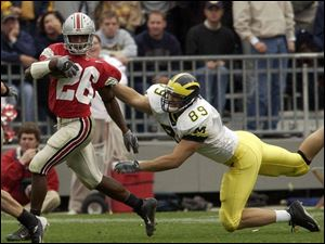Ohio State cornerback Ashton Youboty eludes Michigan's Tyler Ecker after intercepting a pass.