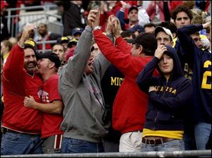 Ohio State fans Dan Fahrer, of Temperance, Mich.; Brian Dennie, an OSU student from Lambertville, Mich.; Bill Dennie (Brian's dad), and Jeff Jeckavitch of Salem, Ohio, celebrate a Buckeyes touchdown, much to the dismay of surrounding Michigan fans in Ohio Stadium.