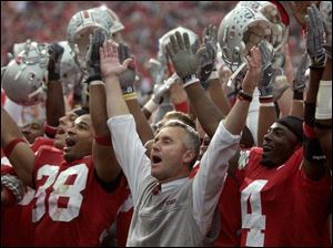 OSU coach Jim Tressel, center, sings 'Carmen Ohio' after the victory over Michigan with players Branden Joe, left, and Santonio Holmes.