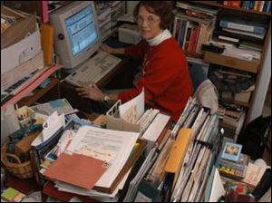 Sharrone Clay in her office, surrounded by books, files, and boxes.