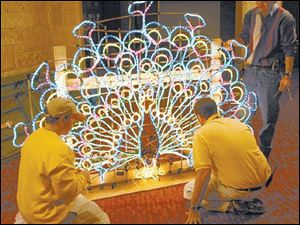 Mike Briggs, Jeff Goodman, and Larry Starkey, from left, work on a light fixture that will be mounted atop a parade float.