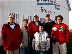 The bicentennial logo provides a backdrop for the Lowe family: Michael, left, Brenda, Jim, Johnny, Brian, and Jimmy. The Ottawa County barn has been in the family since 1930.