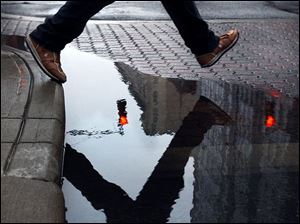 A pedestrian hops a puddle at the corner of North Huron Street and Madison Avenue. That puddle of water should turn into a sheet of ice tonight as the temperature dips into the 20s.