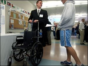 Engineering student Doug Stricker, left, shows Doug Martz the wheelchair extension push handles his team designed.