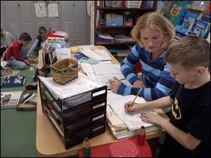 Katie Wendt, a second-grade teacher in Vanlue, works with Gage Parker, 8. Vanlue's superintendent said small schools are costlier to run on a per-pupil basis than bigger school districts.