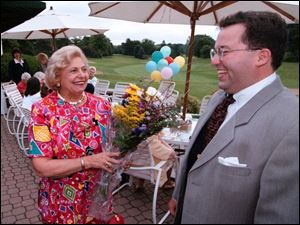 Steven Ambrose, right, surprises Toledo philanthropist Ann Galloway at a birthday party for her at Inverness Club in 1997. Ambrose would enter clubs and events claiming to be Mrs Galloway's nephew. Mrs. Galloway now says Ambrose 'seemed to prey on women who were older.'