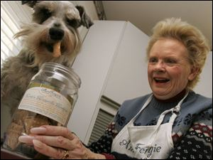 Janice Ferguson gives her dog Monte a sample of the canine snacks she makes at the cooperative kitchen.
