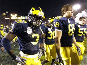Michigan's Marlin Jackson (3), Tyler Ecker (89) and Jeremy Read (55) walk off the field after a Rose Bowl defeat.