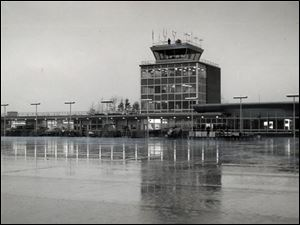 The image of the new airport terminal is reflected off the ice-coated tarmac on Jan. 5, 1955. The airport opened the following day.