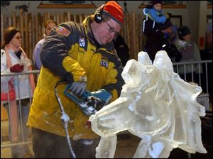 Visitors watch professional carver Robert Childers of Illinois as he works on his sculpture during the competition at the Toledo Zoo. The works can be viewed as long as the weather holds.