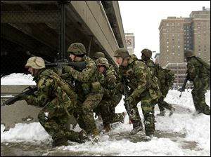 Reservists of the Weapons Company, 1st Battalion, 24th Marines test their urban fighting skills along a downtown street. the blade/dave zapotosky Curious and surprised spectators watch the Marine exercises downtown. James Eggleston of Elyria used his video camera to capture the military training for later viewing.