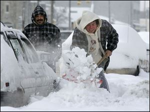 Rito Pizanna, left, takes a breather while Mary Lourdes Palacios battles the packed snow.