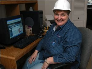 Dorothy Sutter, in a hard hat symbolizing her portfolio's role in industry, chose her stocks in honor of her hometown roots.