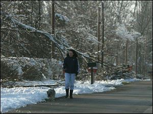 Linda Bearcaw walks her dog along Jo Jean Road in Allen County, where power is expected to be restored by Thursday.