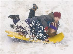 Maumee residents Nicole Figueroa, 14, and Devin Fox, 7, share a ride down an incline at Indian Hills Park. Much of the snow could melt today, as temperatures are expected to reach the middle to upper 50s.
