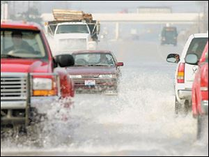 Vehicles slosh through water covering U.S. 20 west of Fremont yesterday.