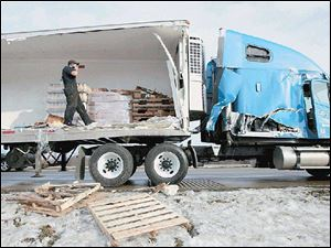 Aaron Myshock unloads orange juice from a crashed tractor-trailer rig on U.S. 23 near Sterns Road.