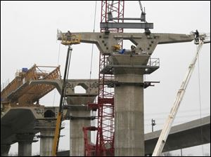 Construction crews using ground-based cranes hoist one of the segments of the new I-280 bridge to its pier-top position.