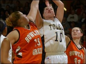 Bowling Green's Liz Honegger attempts to block a show by Toledo's Danielle Bishop as Megan Thorburn watches in last night's game at Savage Hall. Honegger scored 19 for the Falcons. Bushop tallied 17 for the Rockets.