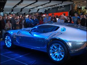 First-day crowds gather around Ford Motor Co. s low-slung Shelby GR-1 concept car at the Detroit car exposition. The auto show in the Cobo Center runs through Sunday.