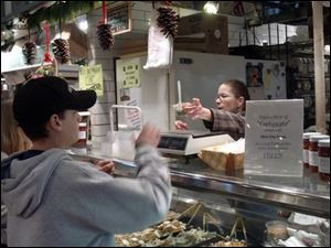 Susan Yacovella, left, manager of the Ohio City Pasta booth at the West Side Market in Cleveland, gives Corbin Wandling, 13, of Akron, a sample of pasta salad.