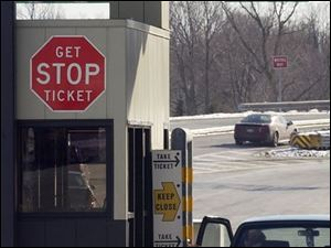 A motorist takes a ticket from a dispenser at the Strongsville interchange of the Ohio Turnpike. If workers strike, the turnpike will charge flat rates for cars, trucks, and big rigs.
