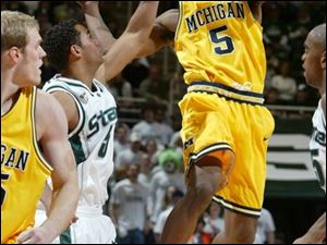 Michigan s Dion Harris makes a pass against Michigan State s Chris Hill. The Wolverines are 12-8, 3-3 Big Ten.