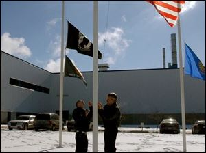 The fl ags outside the Toledo North Assembly plant are lowered to half staff. Production was scheduled to resume today.