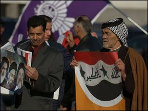 Abas Al-Gazali, left, and his 75-year-old father, Musa, campaign outside the Southgate, Mich., polls for Iraqi expatriates.