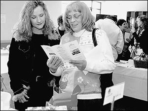 Judi Reese, left, and Debby Sheets look over silent auction items at  The Chocolate Affair  in Sylvania.