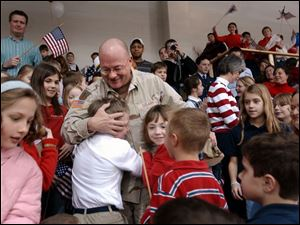 Sgt. Jeff Gagle, elementary principal at Toledo Christian School, is greeted by his students during a welcome-home ceremony.