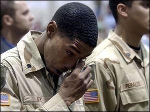 Spec. Joshua Bey of the 216th Engineer Battalion wipes away tears while  Amazing Grace  is played in honor of three fallen comrades. The soldiers were welcomed home yesterday.