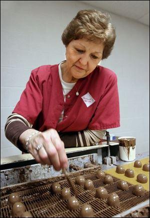 Billie Smith puts the finishing touches on chocolates at Dietsch Brothers.