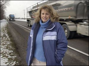Tractor-trailers provide a backdrop along U.S. 24 for Patricia Rupert of Grand Rapids, who is being honored for her efforts in rescuing an injured woman from behind the wheel of a burning van in November.