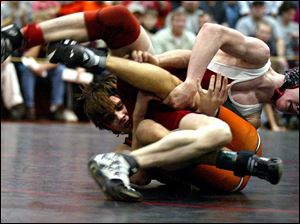 A.J. Scarberry tries to get out from under Arcadia's Lee Shumaker in the 112-pound championship match in the Division III district. Scarberry won with a reversal in the final 20 seconds.