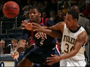 Toledo's Keith Triplett and Southern Methodist's Devon Pearson fight for a loose ball.