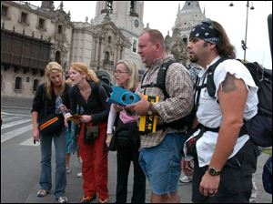 Bianca, Debbie, Susan, Ryan, and Chuck (from left) pause to read a clue in the Plaza de Armas in Lima, Peru, on the special two-hour season premiere of The Amazing Race 7 at 9 tonight.