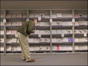 A visitor to the IRS office in 4 SeaGate in downtown Toledo selects from shelves full of taxpayer publications.