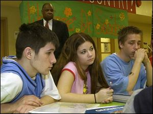 Superintendent Eugene Sanders looks on as Rogers High School sophomores, from left, Mike George, Heather Koralewski, and Cody Jahns, listen to a school presentation of the importance of the upcoming Ohio Graduation Test.