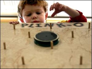 NBR luckey05p 01 - Little Hunter Shiffler, 3, plays plinko at the Luckey Elementary school carnival. The Blade/Allan Detrich