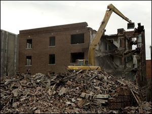 An excavator is used to demolish an apartment building at 2107 Putnam St. that has been vacant since 1957. It had attracted vagrants and drug users to the neighborhood.
