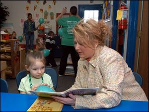 Brandi Chasteen, 6, listens to Ronda Hice, owner of Casey's Castle, read to her at the day-care center on West Alexis Road.