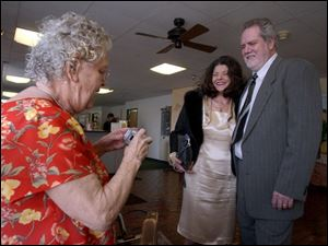 Elsie Baltrip, left, takes a photograph of Lisa and Aaron Simonton as he was honored at the Monroe Senior Center.
