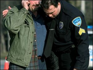Oregon police Sgt. Ken Reno comforts Wayne Appenfelder, whose great-nephew Dameatrius