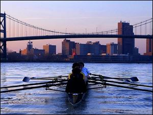 The St. John's crew team practices on the Maumee River as the sun sets behind downtown Toledo.