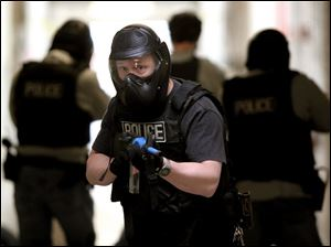 Officers move through the halls of Starr Elementary School during an exercise. The school was closed for spring break.
